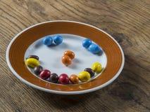 Sorrida dal piatto marrone bianco del bonbon della caramella del colorfull sul de di legno Fotografia Stock
