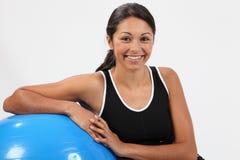 Sorrida dalla giovane donna di misura con la sfera di esercitazione Immagini Stock Libere da Diritti