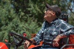 Sorridendo, agricoltore senior sul suo trattore Fotografia Stock