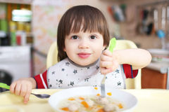 Sorridendo 2 anni di ragazzo che mangia minestra Immagine Stock Libera da Diritti