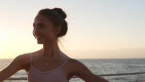 Sorridendo, ballerino di balletto energetico che pratica all'aperto Elementi classici di pratica di balletto seaside Sole di matt archivi video
