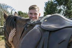 Sorridendo, cavaliere bello del cavallo maschio che sta accanto al cavallo Fotografia Stock