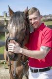 Sorridendo, cavaliere bello del cavallo maschio che sta accanto al cavallo Fotografie Stock