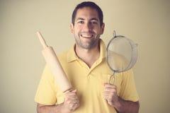 Sorridendo, cucinando gli utensili della tenuta dell'uomo Immagini Stock Libere da Diritti
