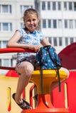 Sorridendo dieci anni della ragazza che si siede con lo zaino in mani sul campo da giuoco dei bambini Immagine Stock