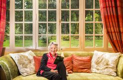 Sorridendo donna senior e grigio-dai capelli, leggente nel suo salotto, Fotografia Stock