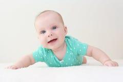 Sorridendo 4 mesi di neonata nella tuta della menta a casa Fotografie Stock Libere da Diritti