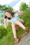 Sorridendo pre ragazza dell'adolescente che rivolge allo smartphone, all'aperto Fotografia Stock