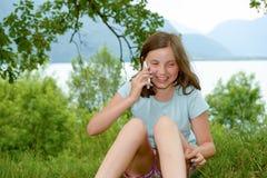 Sorridendo pre ragazza dell'adolescente che rivolge allo smartphone, all'aperto Fotografie Stock Libere da Diritti