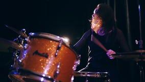 Sorridendo precipitandosi teenager-ragazza con il batterista che esegue con i tamburi, movimento lento di percussione dei capelli archivi video