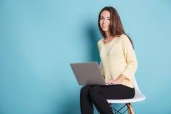 Sorridere abbastanza teenager con il computer del pc del computer portatile sopra fondo blu Fotografia Stock Libera da Diritti