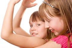 Sorridere allegro delle due ragazze sopra il bianco Fotografia Stock