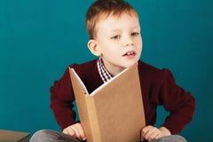 Sorridere allegro poco ragazzo di scuola che si siede su uno scrittorio contro il tur Fotografia Stock Libera da Diritti