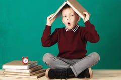 Sorridere allegro poco ragazzo di scuola con i grandi libri pesanti sulla sua h Fotografie Stock Libere da Diritti