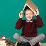 Sorridere allegro poco ragazzo di scuola con i grandi libri pesanti sulla sua h Fotografia Stock Libera da Diritti