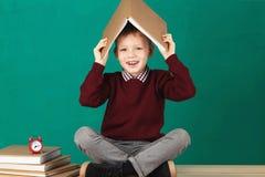 Sorridere allegro poco ragazzo di scuola con i grandi libri pesanti sulla sua h Fotografia Stock