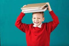 Sorridere allegro poco ragazzo di scuola con i grandi libri sul suo testa ha Fotografia Stock Libera da Diritti