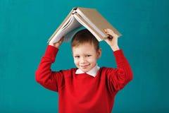 Sorridere allegro poco ragazzo di scuola con i grandi libri sul suo testa ha Fotografia Stock