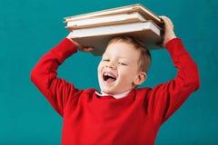 Sorridere allegro poco ragazzo di scuola con i grandi libri sul suo testa ha Fotografie Stock