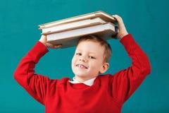 Sorridere allegro poco ragazzo di scuola con i grandi libri sul suo testa ha Immagini Stock