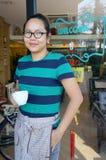 Sorridere asiatico della tazza di caffè della tenuta della cameriera di bar Fotografia Stock