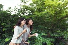 Sorridere ben vestito degli amici felici delle giovani donne mentre stando a Fotografia Stock Libera da Diritti