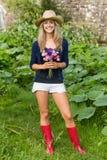 Sorridere biondo grazioso ai fiori della tenuta della macchina fotografica Fotografie Stock Libere da Diritti