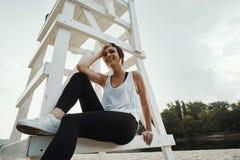 Sorridere castana con breve taglio di capelli che si siede sul sedile di pallavolo Immagine Stock Libera da Diritti