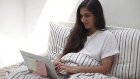 Sorridere castana sta sedendosi a letto appoggiandosi i cuscini e scrivendo sul taccuino video d archivio