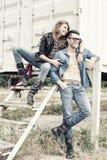 Sorridere da portare dei jeans e dei caricamenti del sistema delle coppie alla moda Fotografia Stock