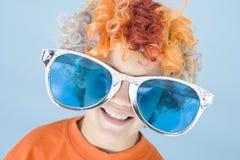 Sorridere da portare della parrucca e degli occhiali da sole del pagliaccio del giovane ragazzo Immagine Stock