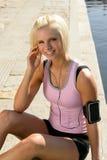Sorridere della donna di sport si distende l'acqua ascolta musica Fotografie Stock