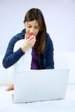 Sorridere della donna mangia la mela che si siede con il calcolatore Fotografia Stock Libera da Diritti