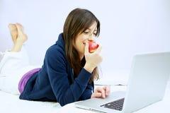 Sorridere della donna mangia la mela davanti al calcolatore Fotografia Stock Libera da Diritti