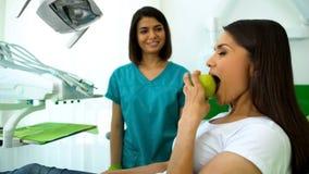 Sorridere dello stomatologo di signora, esaminante mela mordace paziente con i denti sani fotografia stock libera da diritti