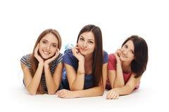 Sorridere di menzogne degli amici di ragazze sul pavimento Immagine Stock Libera da Diritti