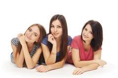 Sorridere di menzogne degli amici di ragazze sul pavimento Fotografia Stock Libera da Diritti