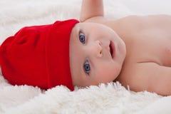 Sorridere di menzogne del neonato adorabile con il cappello rosso sopra Immagine Stock