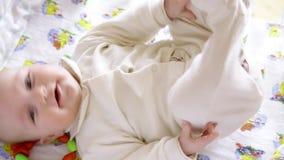 Sorridere di starnuto del ragazzo della ragazza di neonato ed allungare mentre svegliando nel proprio piccolo letto stock footage