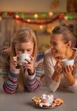 Sorridere due amiche che hanno natale fa un spuntino in cucina immagini stock