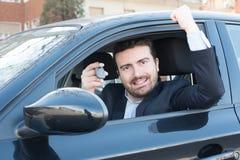 Sorridere felice dell'uomo messo nella sua chiave della tenuta dell'automobile Fotografia Stock Libera da Diritti