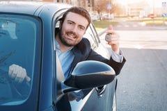 Sorridere felice dell'uomo messo nella sua chiave della tenuta dell'automobile Immagine Stock Libera da Diritti