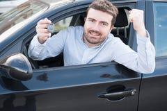 Sorridere felice dell'uomo messo nella sua chiave della tenuta dell'automobile Fotografia Stock