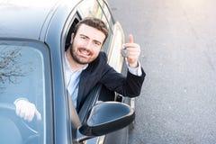 Sorridere felice dell'uomo messo nella sua chiave della tenuta dell'automobile Fotografie Stock Libere da Diritti