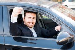 Sorridere felice dell'uomo messo nella sua chiave della tenuta dell'automobile Immagini Stock