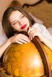 Sorridere felice della bella studentessa castana attraente elegante della giovane donna con il rossetto rosso a cercare del globo Immagini Stock Libere da Diritti