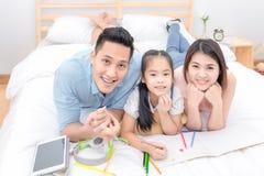 Sorridere felice della famiglia asiatica e si rilassa sul letto a casa Fotografia Stock Libera da Diritti