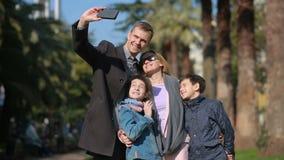 Sorridere felice della famiglia La gente è fotografata su un telefono cellulare che passeggia lungo la via archivi video