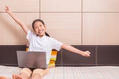 Sorridere felice e ragazza asiatica eccitata che usando il noteb del computer portatile del computer Fotografia Stock