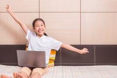 Sorridere felice e ragazza asiatica eccitata che usando il noteb del computer portatile del computer Immagine Stock Libera da Diritti